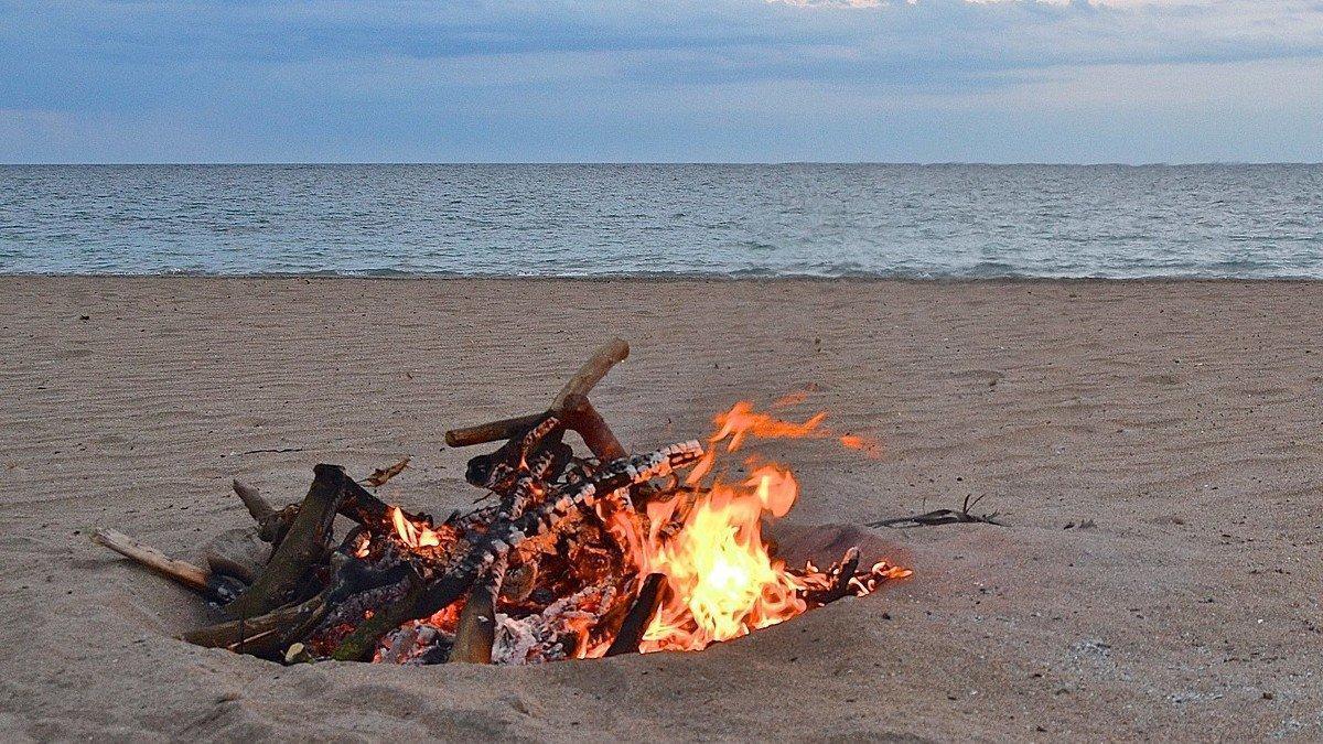 Hoguera quemando en la arena de la playa.
