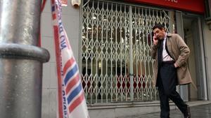 Un ciutadà parla per telèfon aquest dimecres al migdia davant l'aparador destrossat de la botiga de telefonia mòbil de la Rambla d'Anselm Clavé de Cornellà.