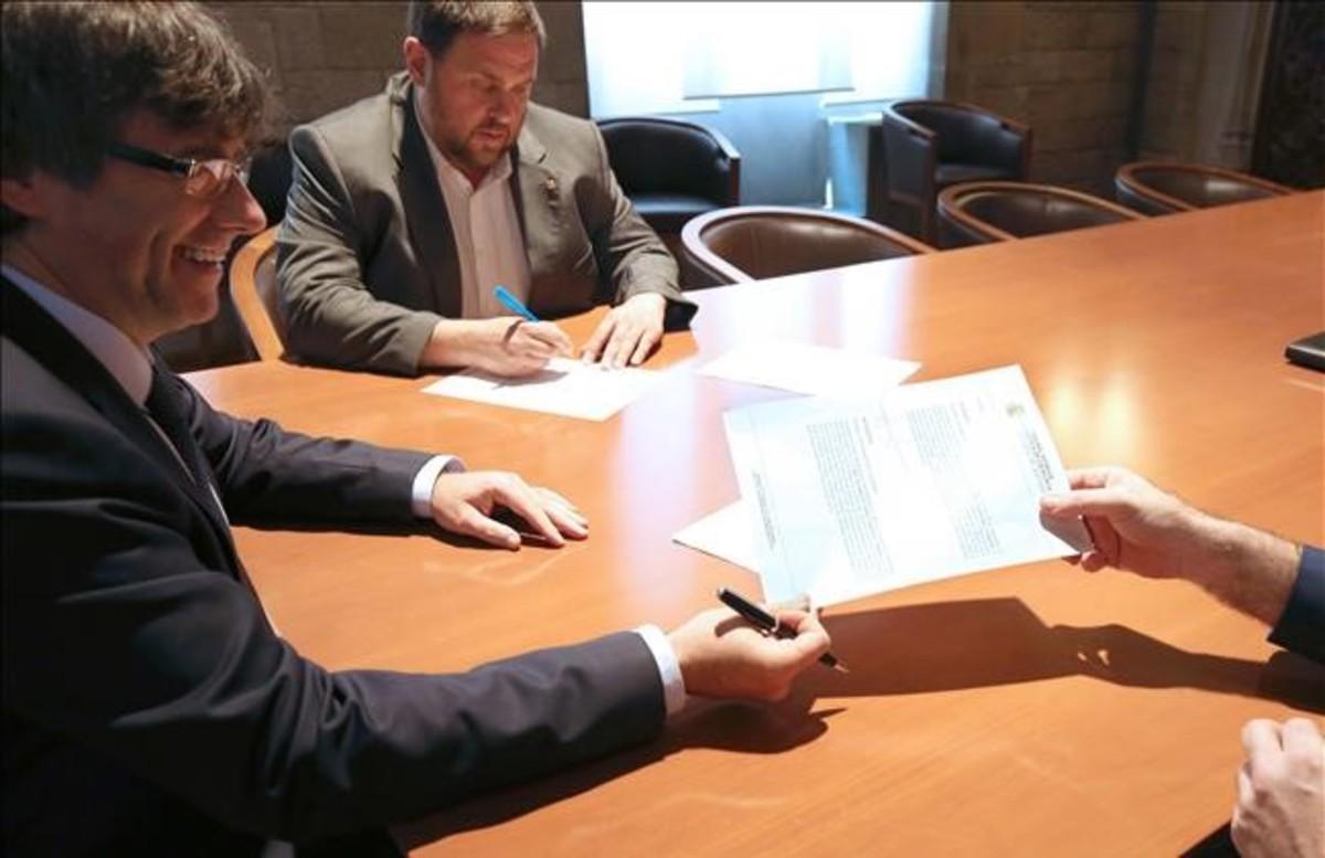 Carles Puigdemont y Oriol Junqueras reciben la notificación del Tribunal Constitucional, este martes en el Palau de la Generalitat.