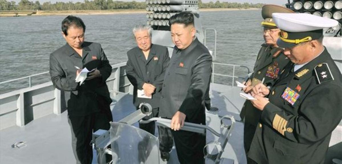 Kim Jong-un (centro) inspecciona un nuevo navío militar, en una foto facilitada el 12 de octubre por el régimen norcoreano, sin especificar la fecha del acto.