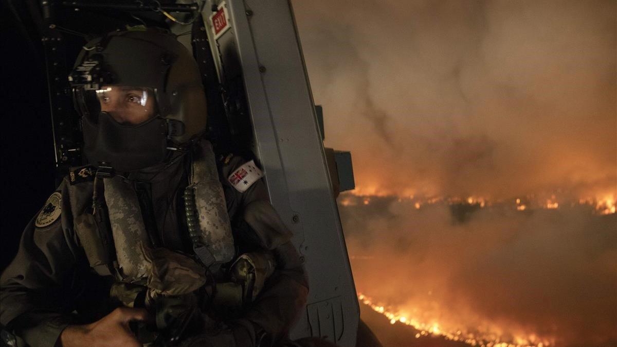 Un miembro de los equipos quetrabajan para sofocar los incendios a bordo de un helicóptero en al parque nacional de Jerrawangala, en Moreton.