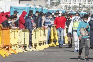 Varios inmigrantes hacen cola en el Muelle de Arguineguín, en Gran Canaria, Canarias (España), a 18 de noviembre de 2020. Más de 2.300 migrantes permanecen hacinados en este muelle tras pernoctar en el campamento que se instaló el pasado mes de agosto en el recinto portuario.