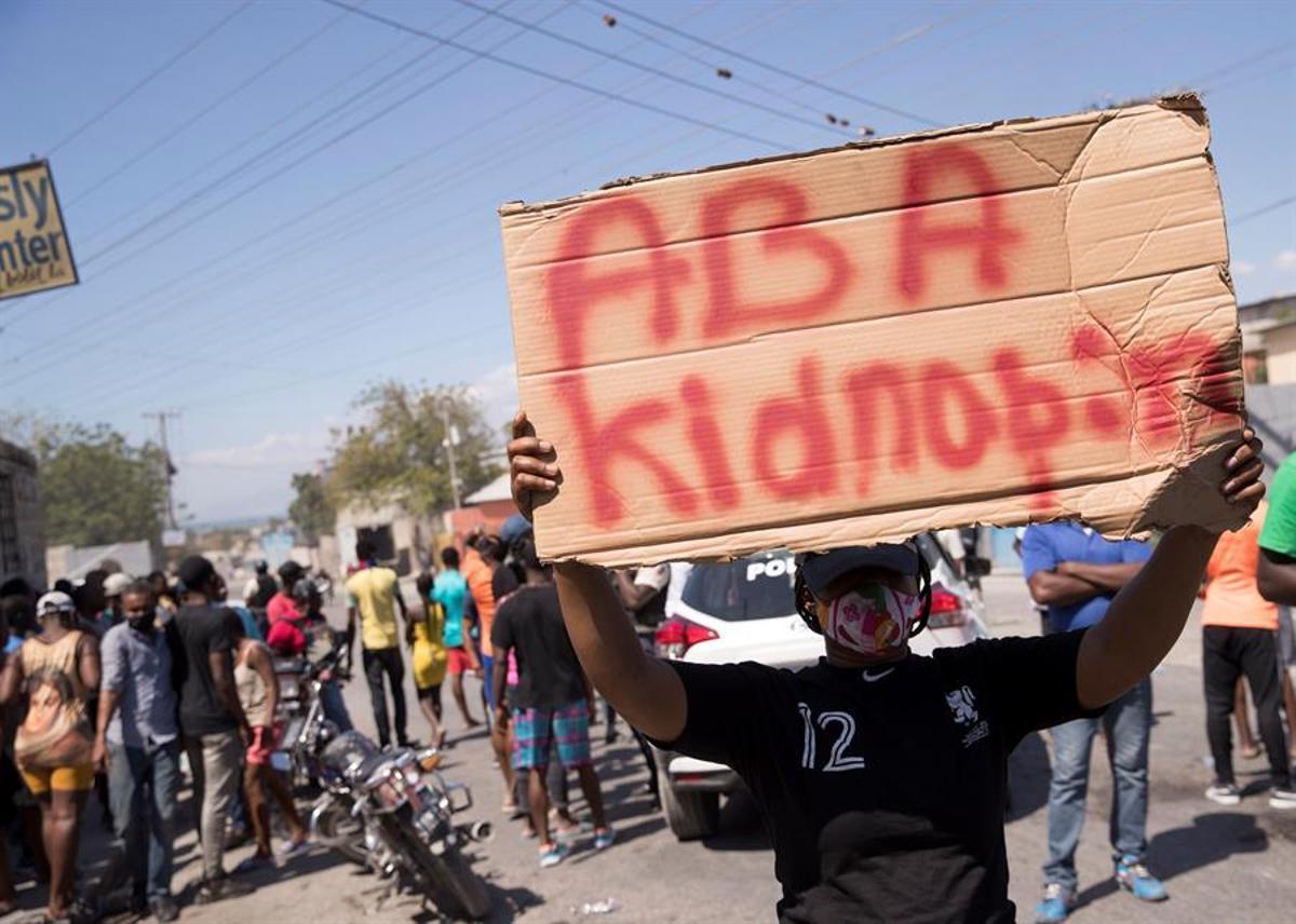 Un grupo de manifestantes grita arengas y carga letreros con la frase Abajo los secuestros en Haití.