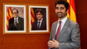 El 'conseller' de Políticas Digitales y Administración Pública, Jordi Puigneró, ante los retratos de Torra y Puigdemont.