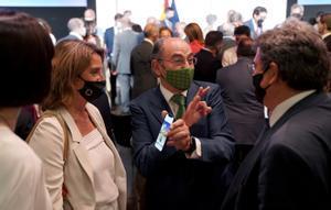 El presidente de Iberdrola, Ignacio Sánchez Galán, muestra su móvil a la vicepresidenta tercera y ministra de Transición Ecológica, Teresa Ribera, mientras conversa con el ministro de Seguridad Social, José Luis Escrivá.