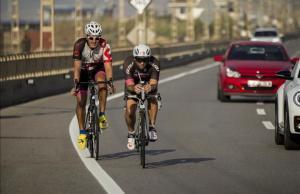 Dos ciclistas entrenan la mañana del viernes por la N-II, en Arenys de Mar, mientras los coches les pasan dejando un mínimo de 1,5 metros.
