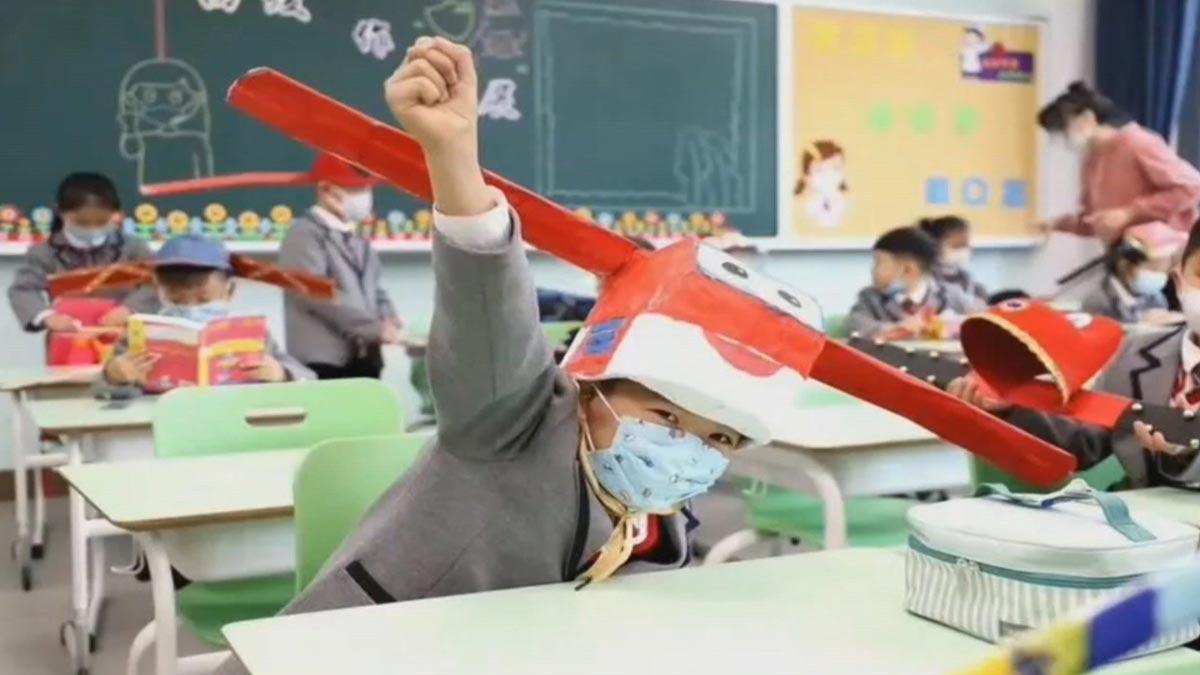 Los niños chinos aprenden distancia social usando sombreros con alas.