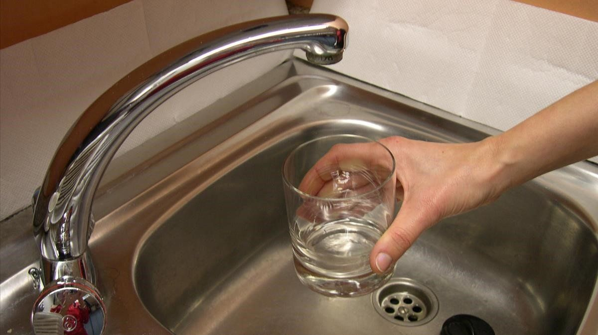 Una persona se dispone a llenar agua del grifo.