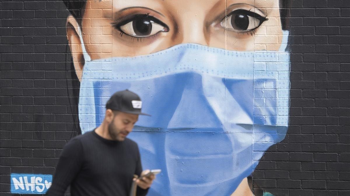 Un hombre pasa junto a un mural que representa a una enfermera con uniforme médico y mascarilla en el área de Shoreditch, al este de Londres.