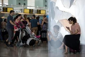 Uns passatgers consulten els seus 'smartphones' a l'aeroport del Prat, aquest estiu.
