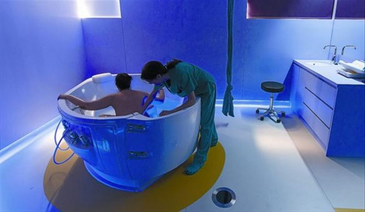 Una parturienta, en la bañera de la Maternitat del Clínic, asistida por una comadrona, ayer.
