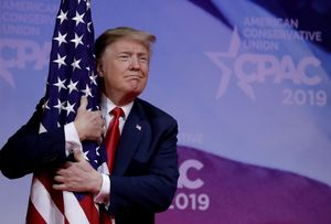 FILE PHOTO  U S  President Donald Trump hugs American flag at the Conservative Political Action Conference  CPAC  annual meeting at National Harbor near Washington  U S   March 2  2019  REUTERS Yuri Gripas File Photo