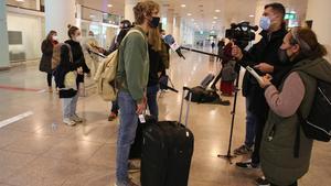 Pasajeros procedentes de Londres atienden a los periodistas a su llegada, este martes, al aeropuerto del Prat.