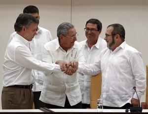 Raúl Castro sostiene las manos estrechadas del presidente de Colombia, Juan Manuel Santos, y del líder de las FARC, Rodrigo Londoño, alias 'Timochenko', este miércoles en La Habana.