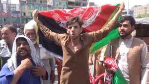 Civiles afganos protestan contra los talibanes con una bandera de Afganistán.