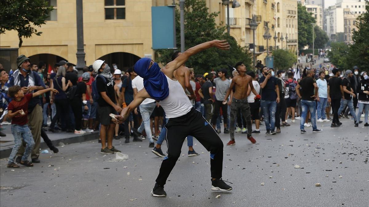 Un manifestante lanza una piedra contra la policía durante las protestas en Beirut, este martes.