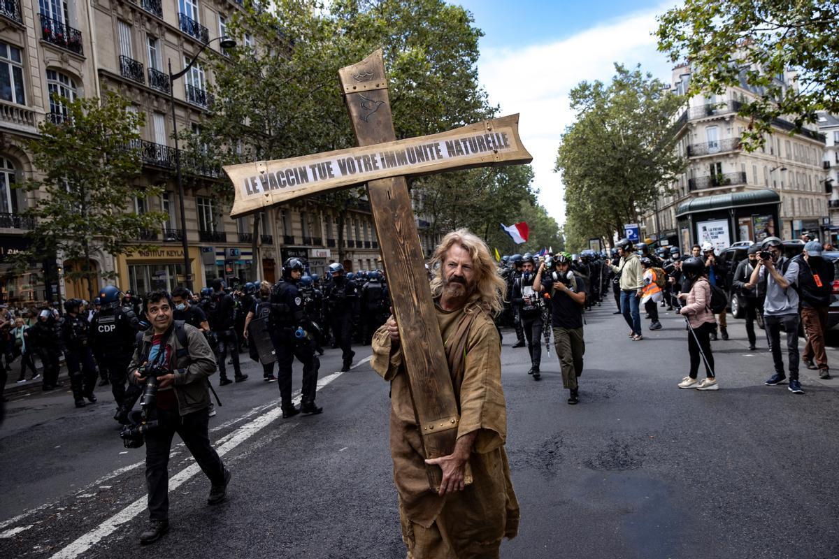 Un manifestante carga con una cruz con el mensaje La vacuna mata tu inmunidad natural , este sábado en la protesta de París.