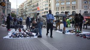 Un grupo de manteros venden sus productos a los turistas este domingo en Plaza Catalunya