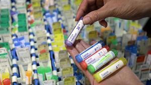 Un homeópata muestra varias diluciones supuestamente medicinales, en una farmacia de Niza.