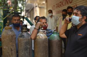 Vecinos de Nueva Deli hacen cola para llenar sus bombonas de oxígeno, este jueves.