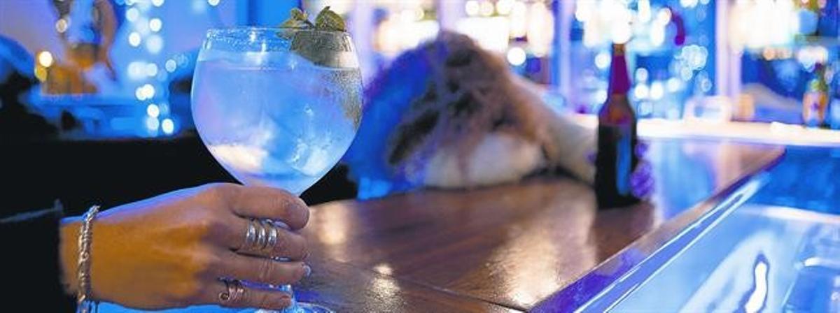 Una mujer consume una bebida en la barra de un bar.