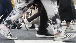 Barcelona     07 12 2020      Sociedad   Aumenta el uso de las zapatillas deportivas como calzado diario  En la foto    desfile de  sneakers   cruzando la calle Aragon   Fotografia de Jordi Cotrina