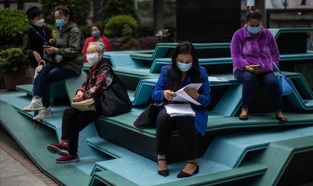 Un grupo de mujeres usan mascarillas y mantienen la distancia preventiva para evitar el contagio del coronavirus, en Hong Kong.
