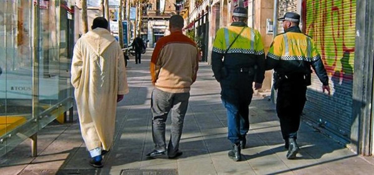 Inmigrantes y agentes de la Guardia Urbana pasean por la rambla del Raval, el pasado viernes.