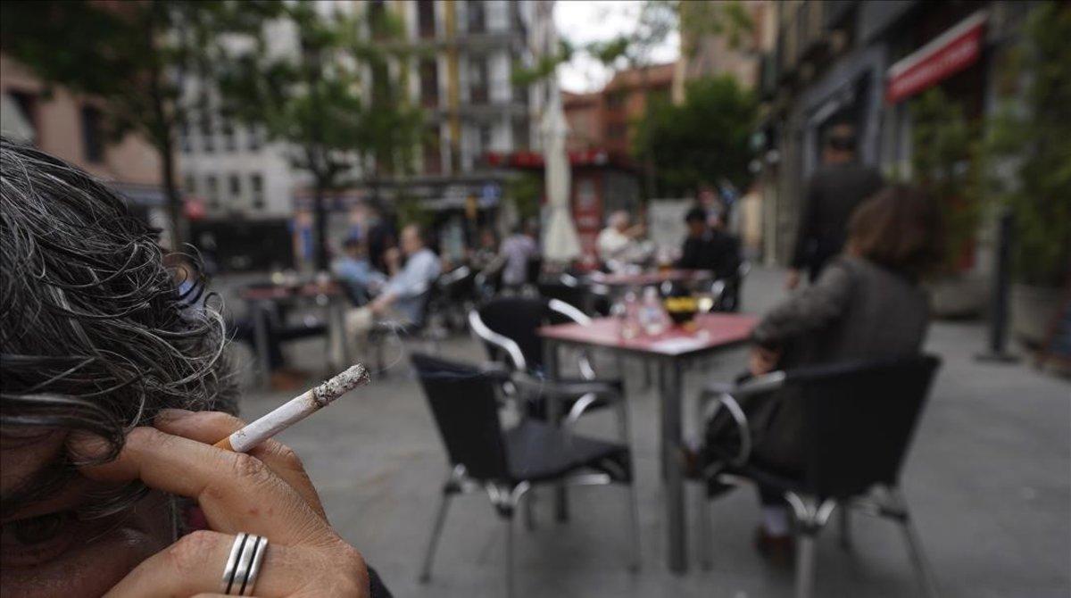 Una persona fuma en la terraza de un bar de Madrid, que está en la fase 1 de la desescalada.