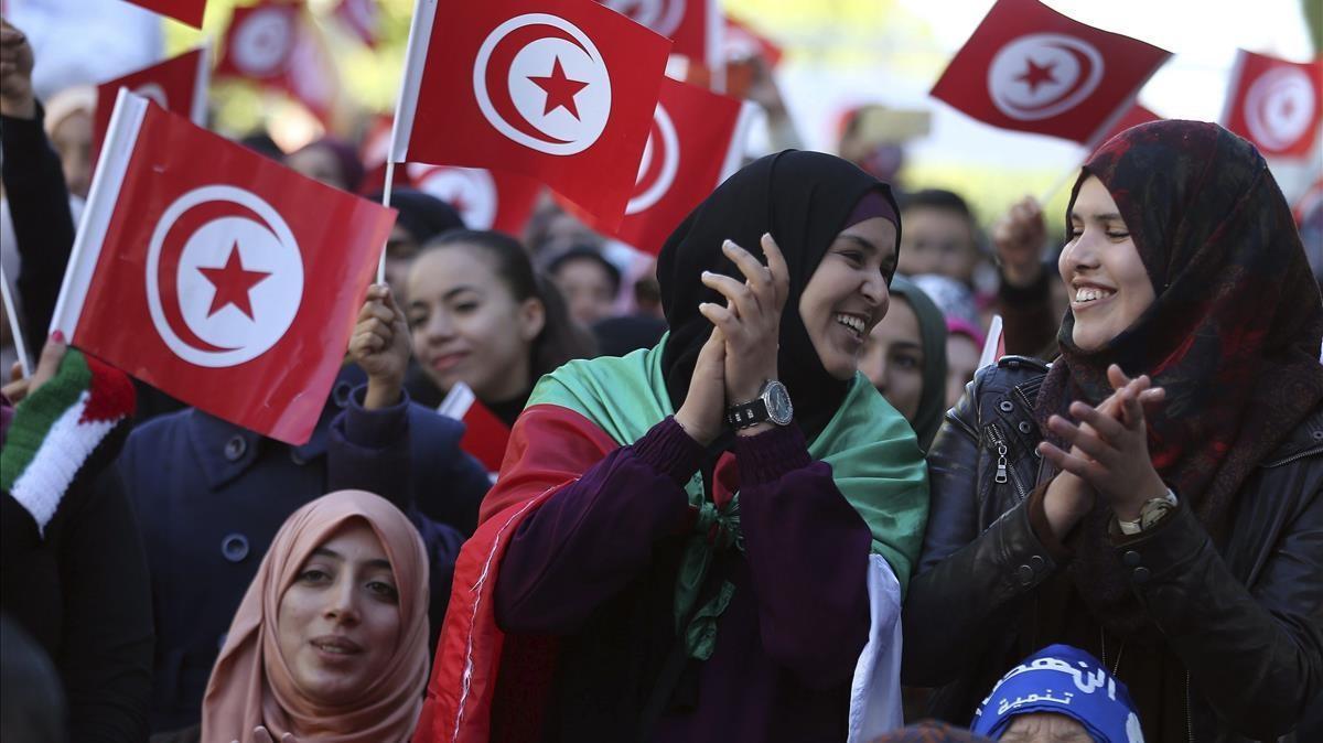 Varias mujeres ondean banderas nacionales durante la celebración del quinto aniversario de la caída de la dictadura de Ben Alí en la avenida Habib Bourguiba, en Túnez.
