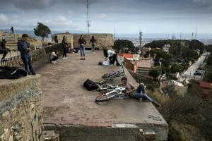 Varias personas contemplan las vistas de Barcelona invadiendo una zona de la batería antiaérea de acceso restringido.