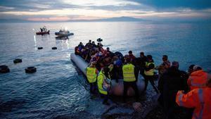 Un grupo de refugiados llega en un bote inflable desde Turquía a la isla griega de Lesbos, cerca de la ciudad portuaria de Mitilini.