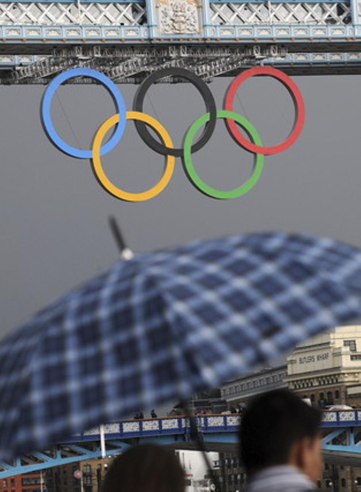 Una pareja se resguarda de la lluvia en la inmediaciones de la ciudad olímpica de Londres, el viernes 20 de julio de 2012.