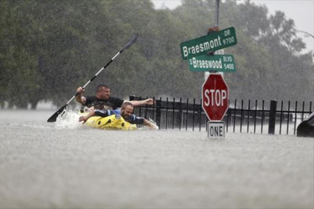 Dos personas tratan de ponerse a salvo de las inundaciones a bordo de un kayak hinchable en una calle de Houston.