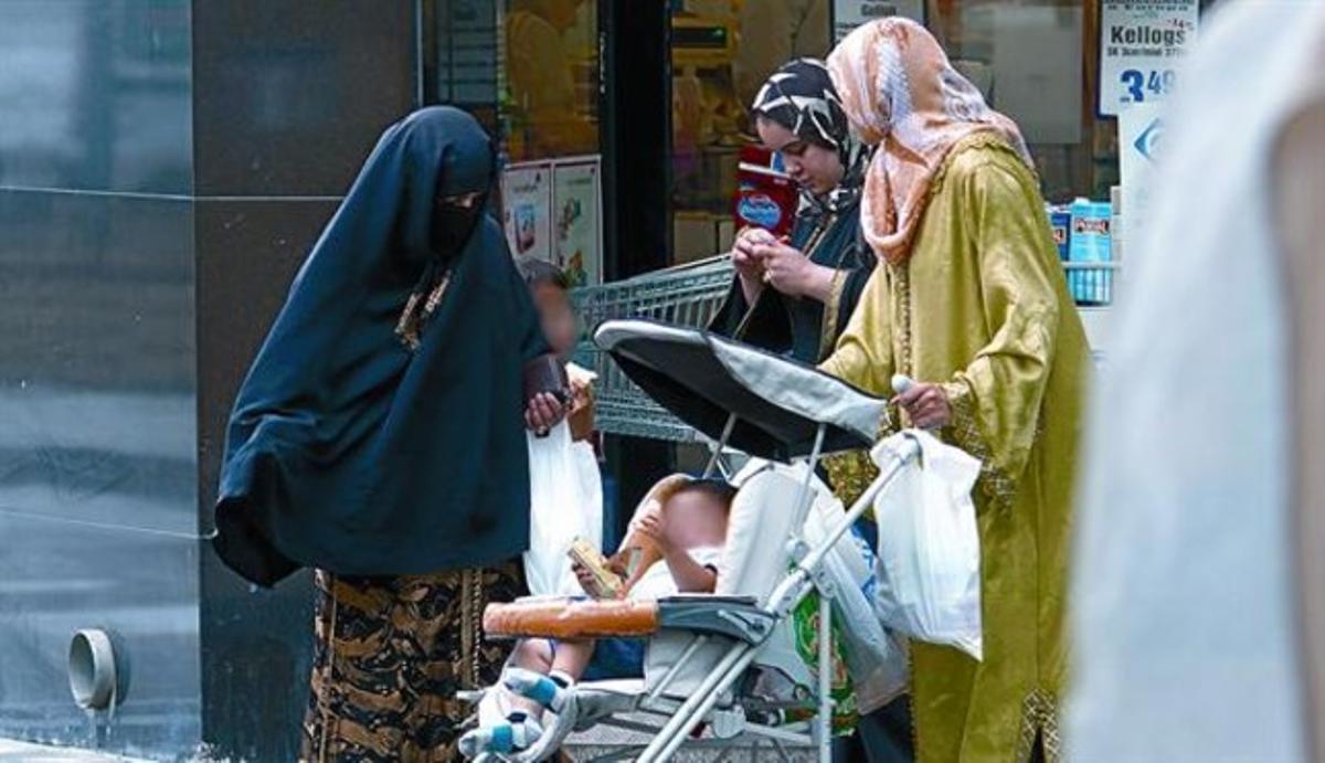 Una mujer con velo integral, junto a otras dos vestidas con el hiyab, el pasado viernes en El Vendrell.