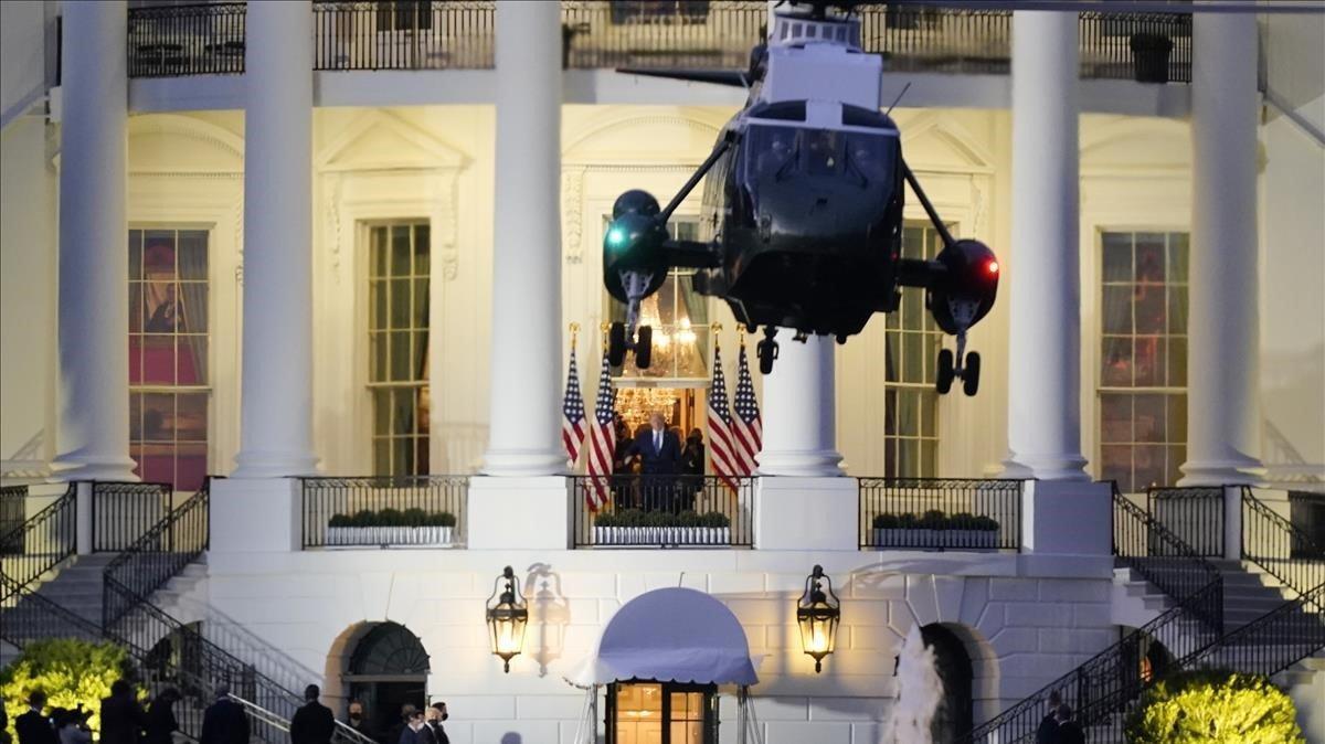 Trump al fondo de la imagen, en el balcón Truman de la Casa Blanca, despide al helicóptero que le trajo desde el hospital.
