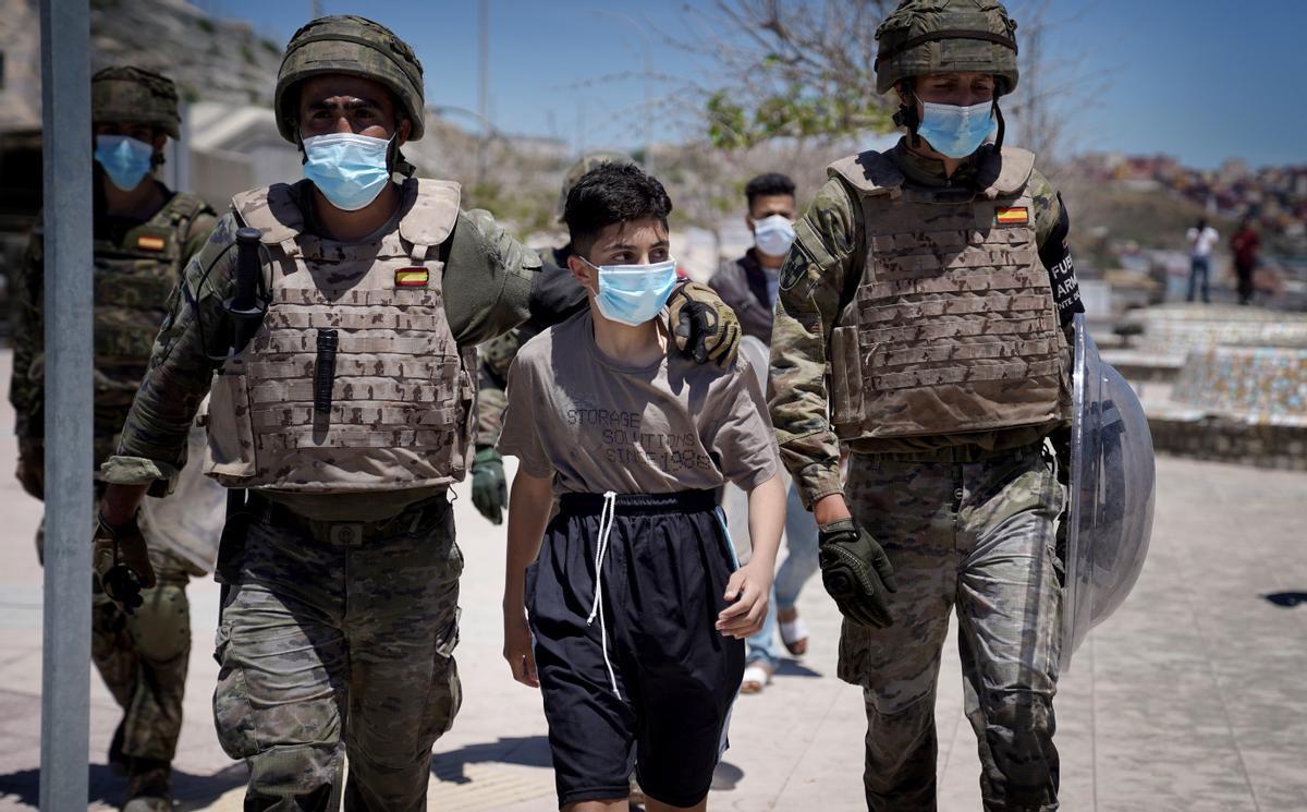 Militares españoles conducen a un menor en la frontera del Tarajal, Ceuta, el pasado 19 de mayo.