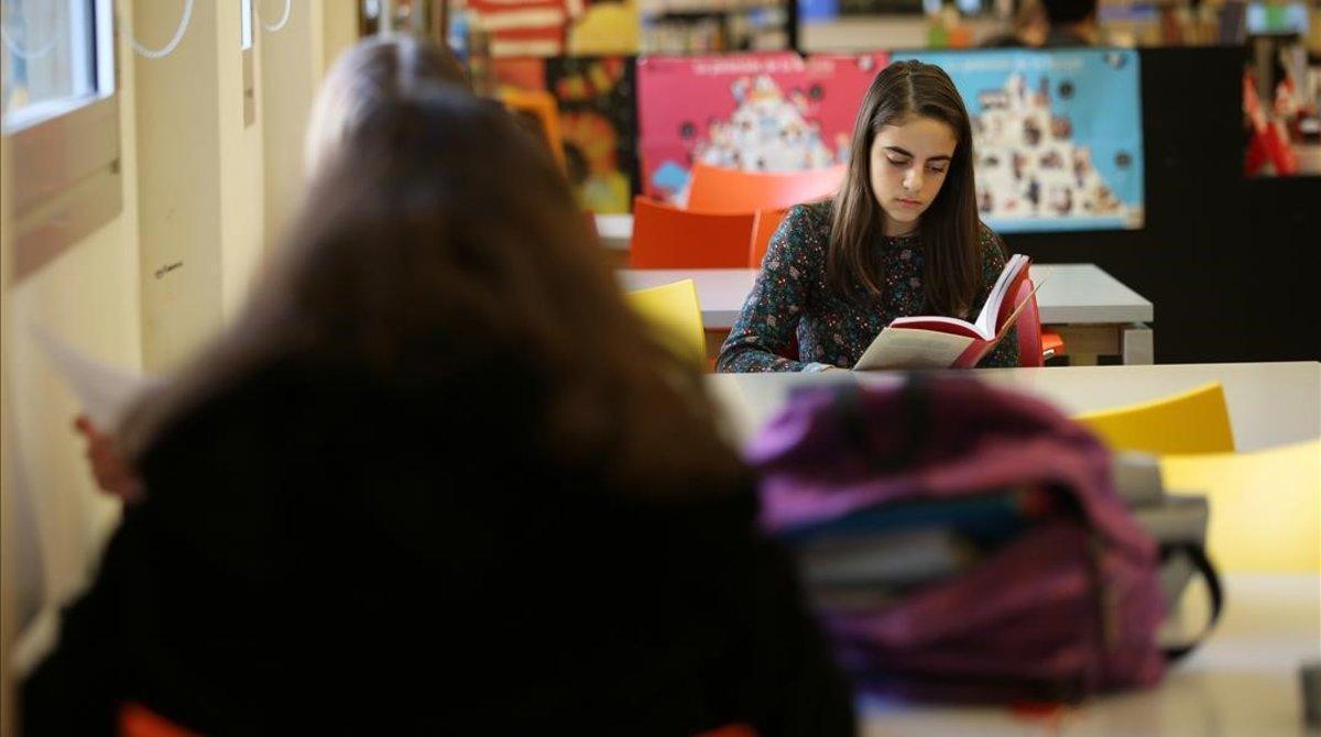 Dos adolescentes leen libros en la biblioteca de Poblenou Manuel Arranz.
