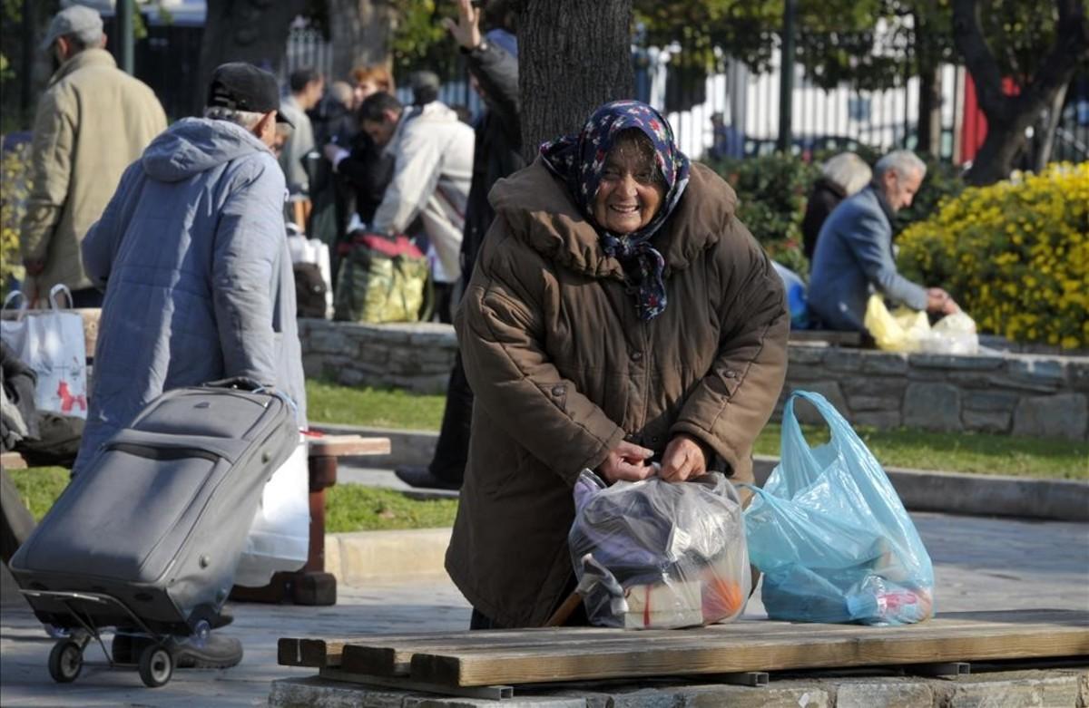 Una anciana sintecho recoge sus pertenencias en Atenas.