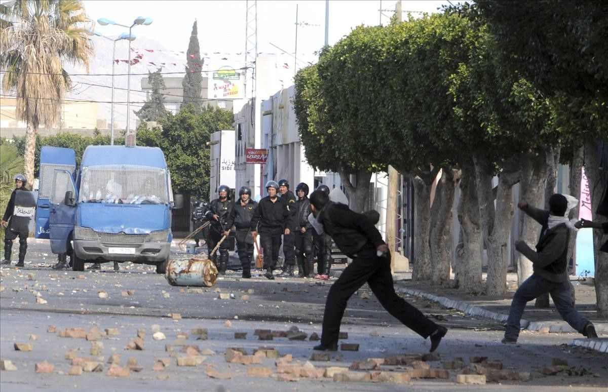 Demonstrators throw stones at police officers in Sidi Bouzid  Tunisia  Monday Jan  10  2011  Tunisia s Interior Ministry said Monday that 14 people were killed in weekend rioting in three towns in the deadliest episodes in more than three weeks of unusual unrest in this popular tourist destination  Union officials around Tunisia have provided their own death counts  higher than the official number  (AP Photo)