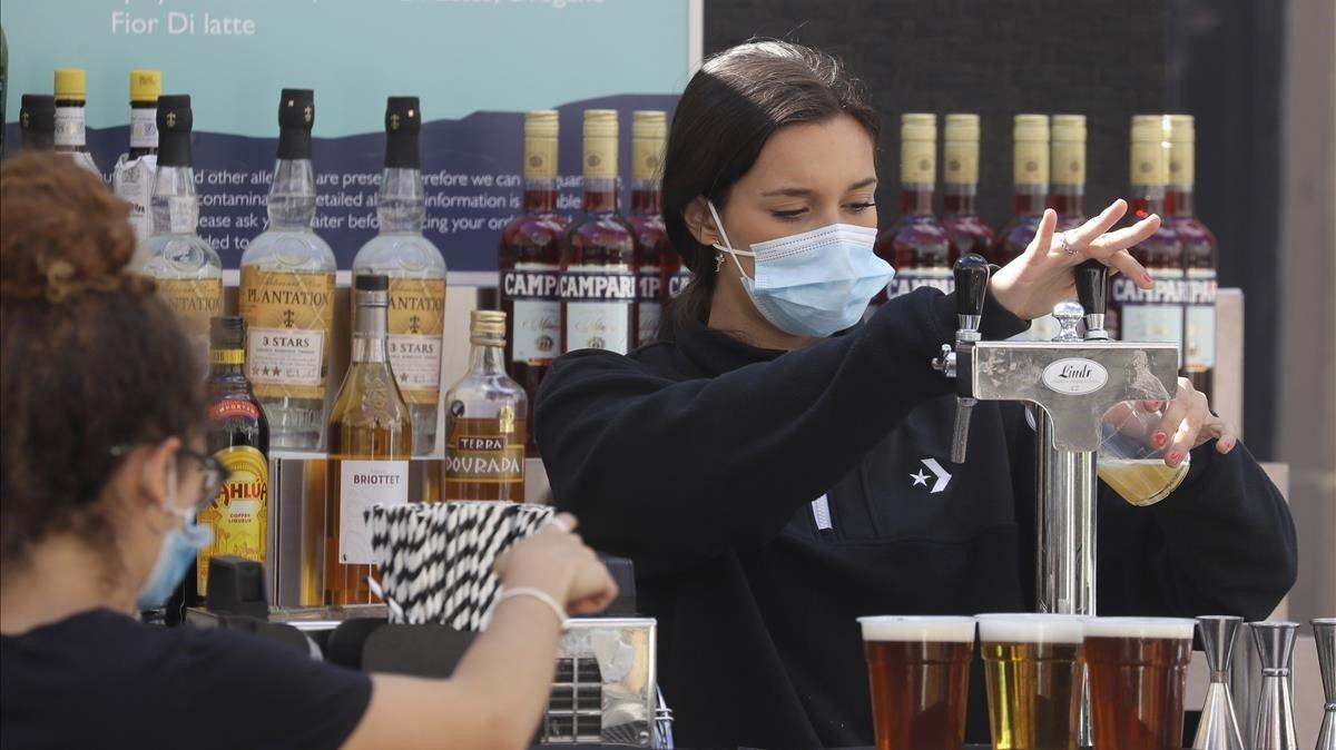 Una empleada sirve una jarra de cerveza en el exterior de un bar en Londres este jueves.