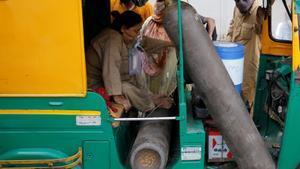 Una mujer es atendida con oxígeno dentro de un vehículo mientras espera ser atendida en un hospital en Ahmedabad, la India.