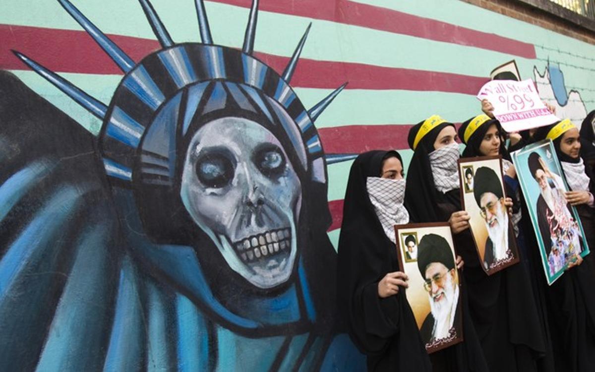 Estudiantes iranís sostienen fotos del ayatolá Jamenei ante el muro de la antigua Embajada de EEUU en Teherán, el viernes, durante los actos de celebración de la toma de la legación estadounidense, hace 32 años.