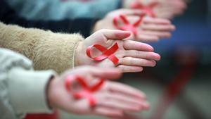 Estudiantes de la Universidad de Yangzhou (China) muestran cintas rojas para promover la prevención del sida, ayer.