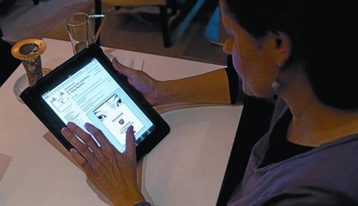 Una lectora consulta la aplicación para Ipad de 'La devoción del sospechoso X', de Keigo Higashino.