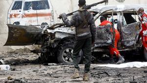 Un policía vigila a los miembros de la Cruz Roja mientras sacan el cuerpo de una de las víctimas del atentado de Al Shabab.
