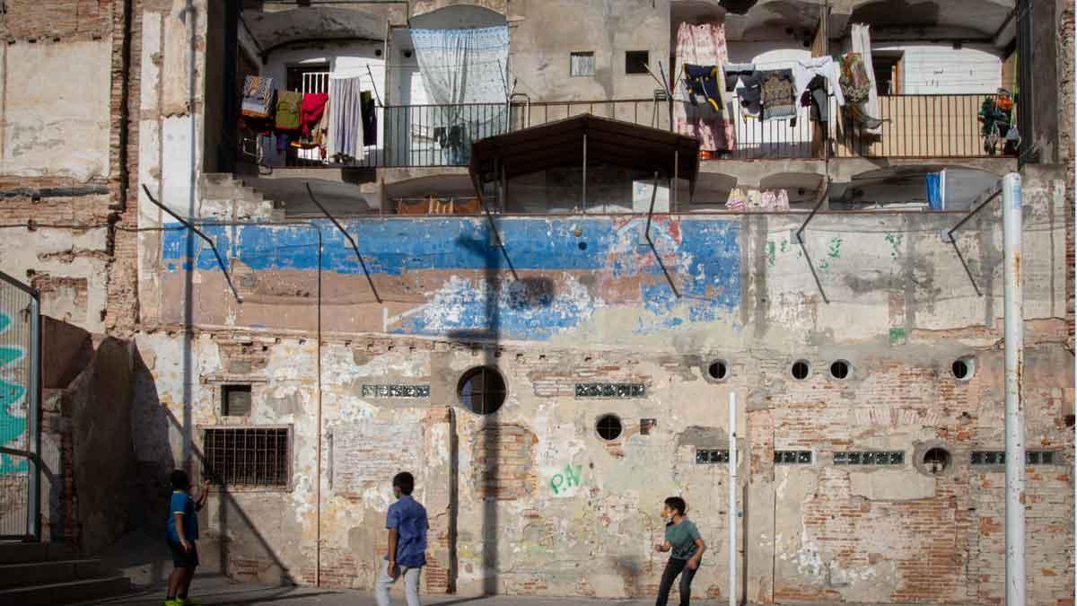 Unos niños juegan junto a una finca del barrio del Raval, en Barcelona.