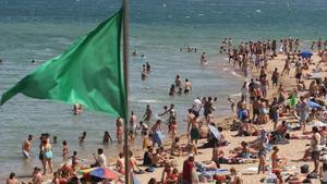 La bandera verde ondea en una playa de la Barceloneta.