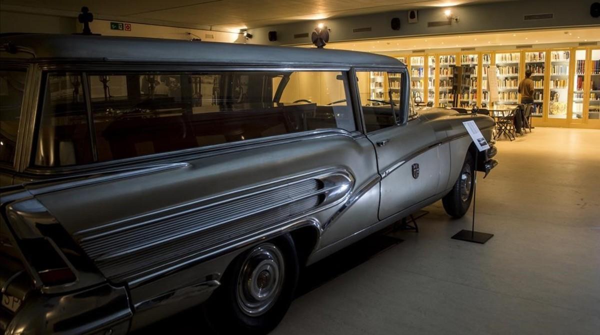Al fondo, Adrià Terol consulta unos libros enla biblioteca funeraria instalada enel cementerio de Montjuïc, junto a la colección de carrozas fúnebres.En primer plano, un Buick del 58 con su ataúd.