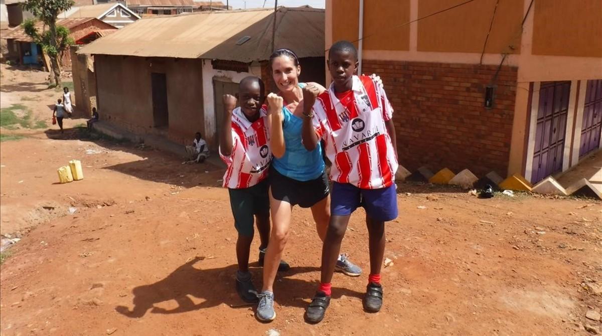 Patricia Campos Doménech, junto a dos niños, en Kajjansi, una pequeña aldea deUganda donde llevaa cabo su labor solidaria.